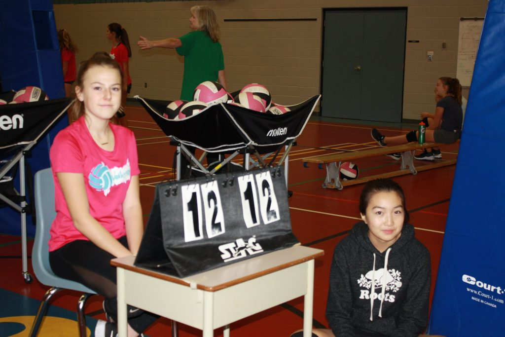 VolleyGirls is always teaching. Continuing education in the summer, two girls learning how to keep score duringa volleyball game at Volleygirls in Burlington, Ontario